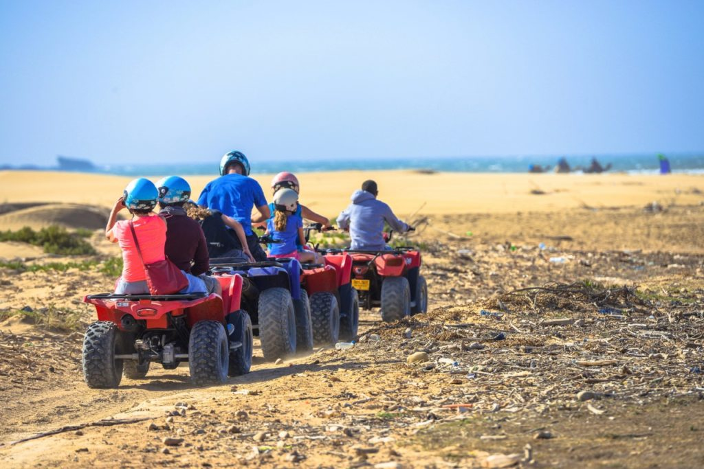 A caraavan of three quads crowded with kids driving through deserted countryside road towards the sea