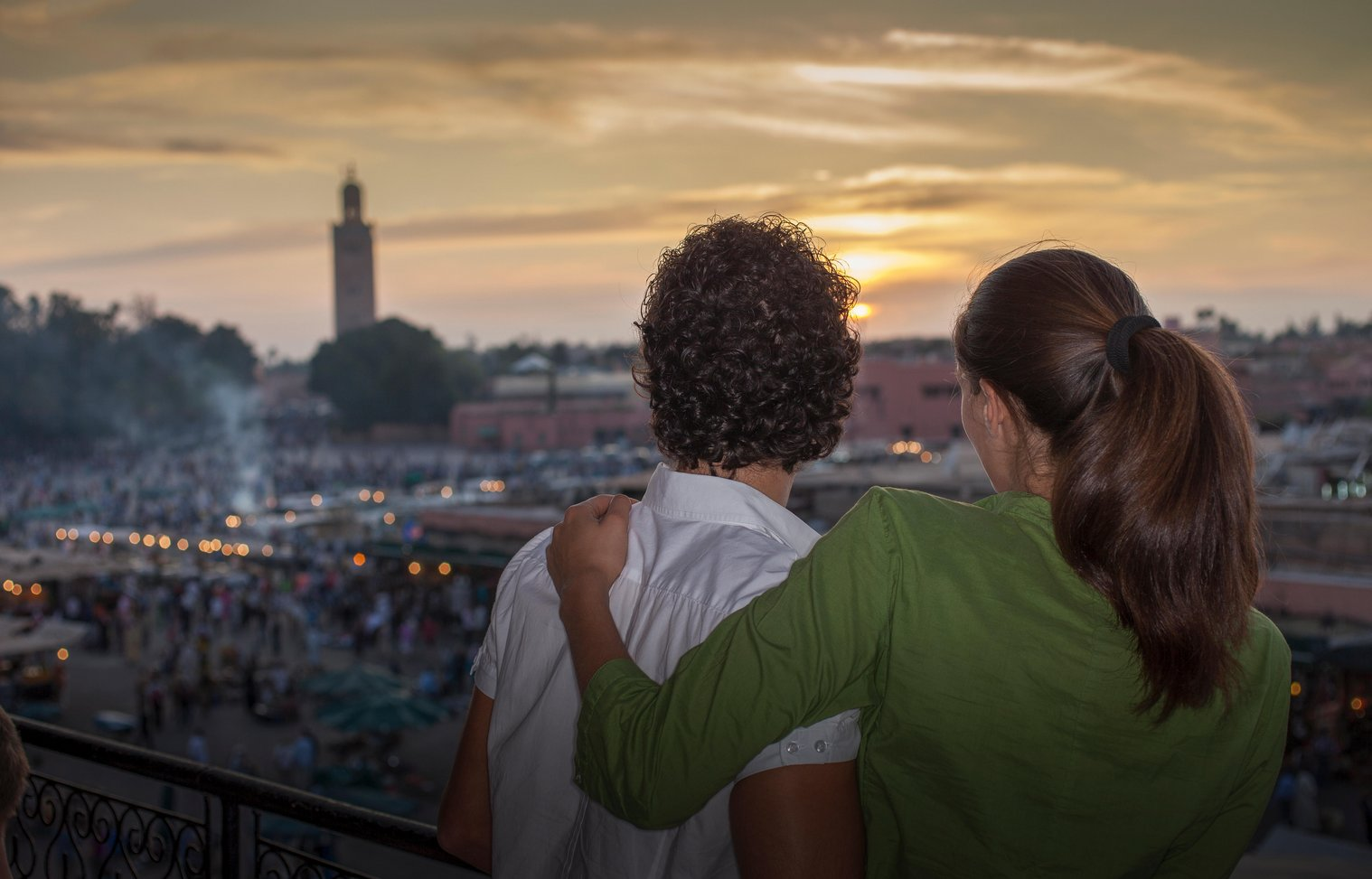 Rear view of couple looking at sunset over Jemaa el-Fnaa Square at sunset, Marrakesh, Morocco