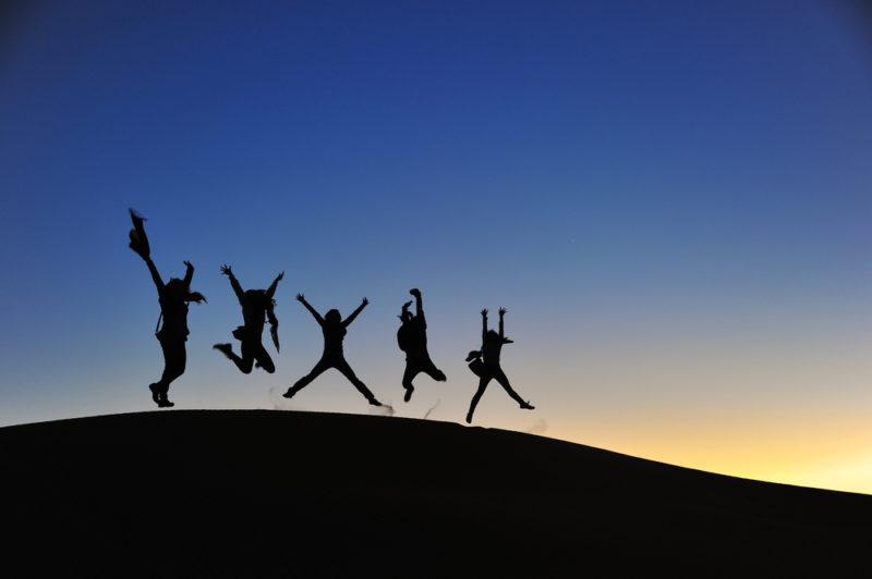 Grupo de viajeros saltando las dunas de Merzouga fin del año